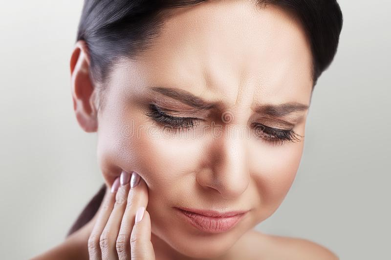 Toothache in a young beautiful woman. Caries. A woman holds her hand in the teeth area. A painful sensation. The concept of health stock images