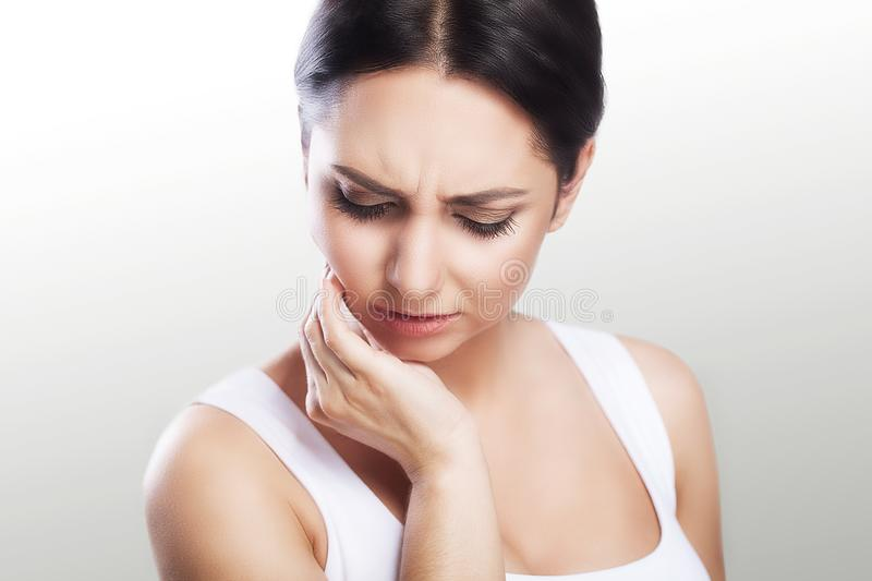 Toothache in a young beautiful woman. Caries. A woman holds her hand in the teeth area. A painful sensation. The concept of health royalty free stock photography