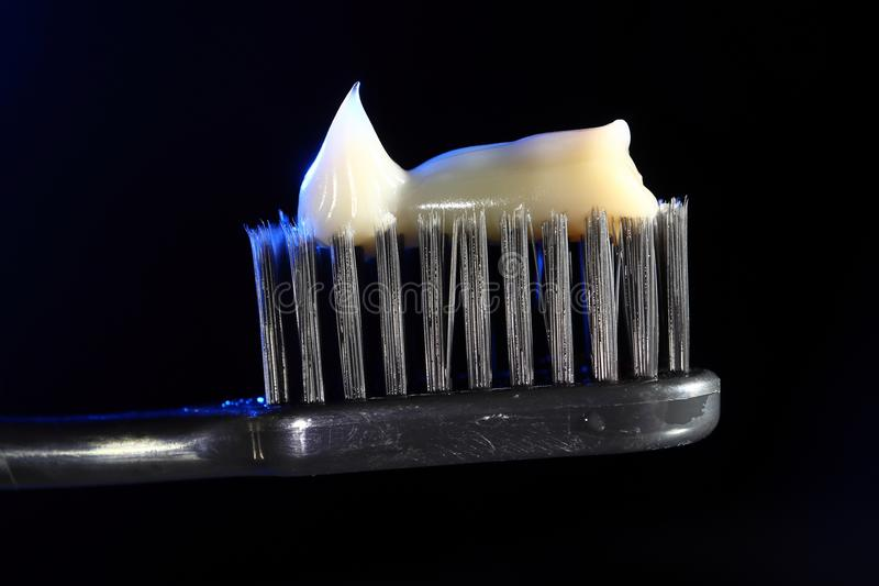 Toothbrush on a black background with cream colored paste.  stock photography