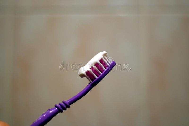 Toothbrush with paste on wall background. Toothbrush with toothpaste against the wall in the bathroom stock image