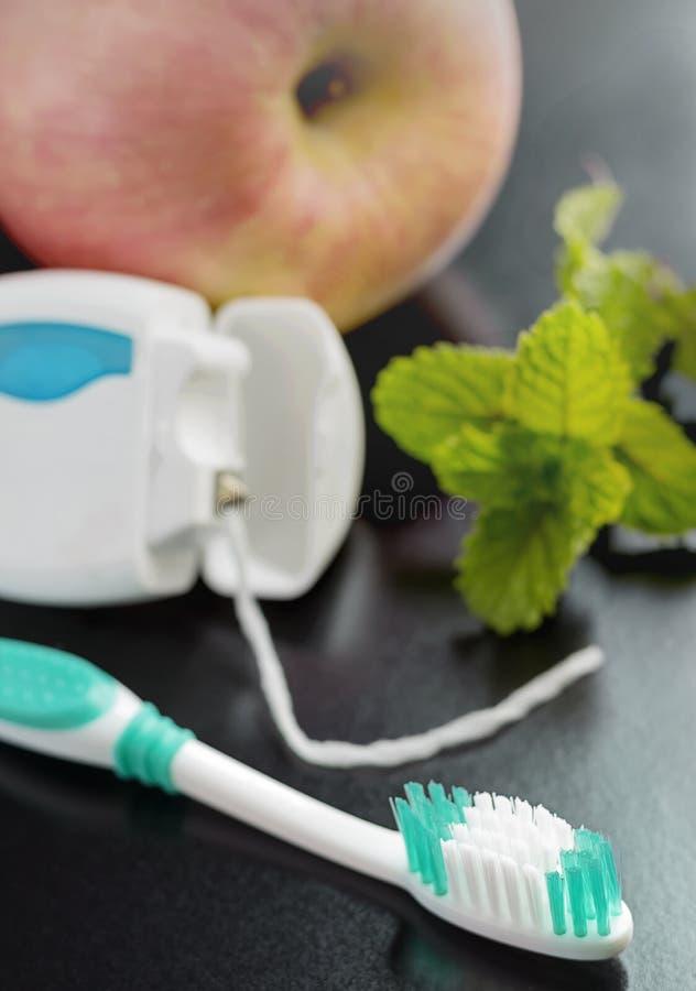 Toothbrush, stomatologiczny floss, jabłko i miętówka na stole, zdjęcie royalty free
