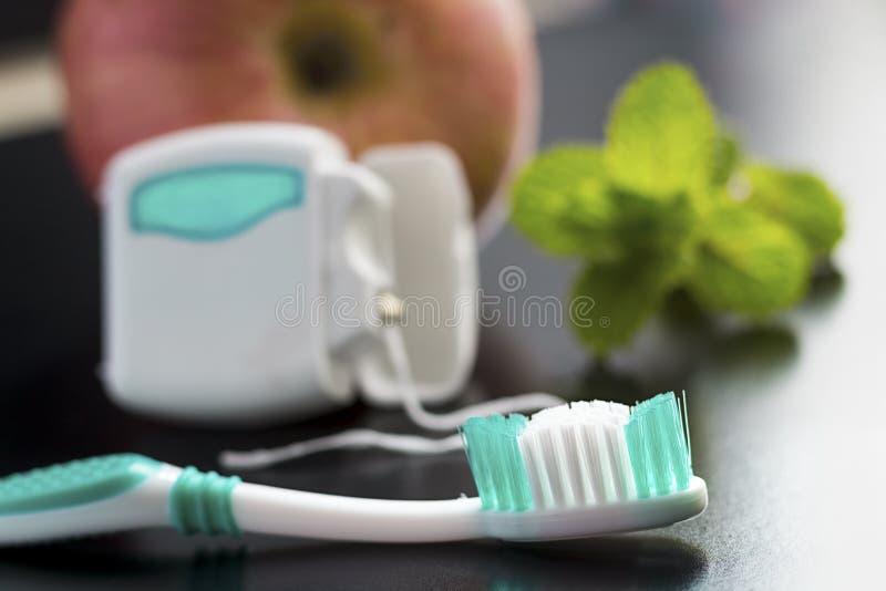Toothbrush, stomatologiczny floss, jabłko i miętówka na stole, obraz stock