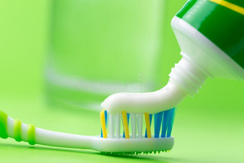 Toothbrush and toothpaste. Close up of squeezing toothpaste on toothbrush on green background royalty free stock images