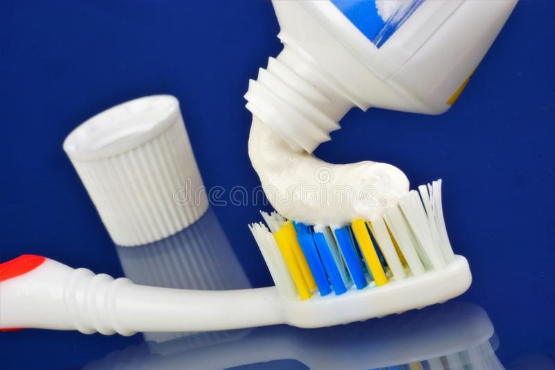 Toothbrush and a tube of toothpaste on a blue background. Oral hygiene products - toothbrush — a device for brushing teeth and. Gum massage, used with stock image