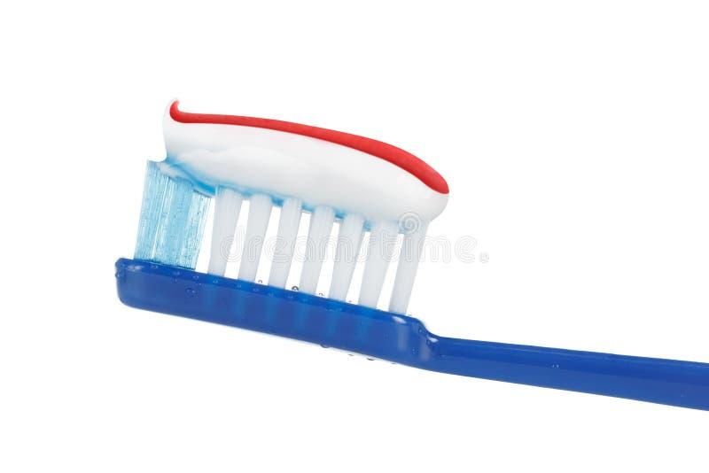 Toothbrush z pasta do zębów makro- odosobnionym na bielu fotografia stock