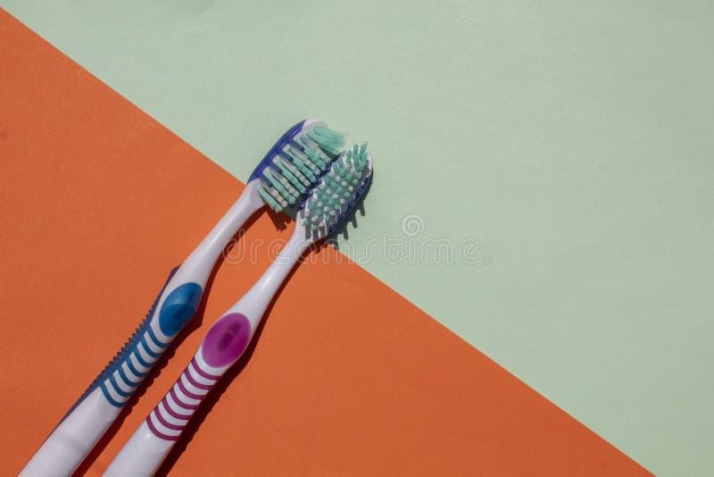 2 toothbrushes, błękit i menchii, Odizolowywający na zielonym i pomarańczowym tle obrazy stock