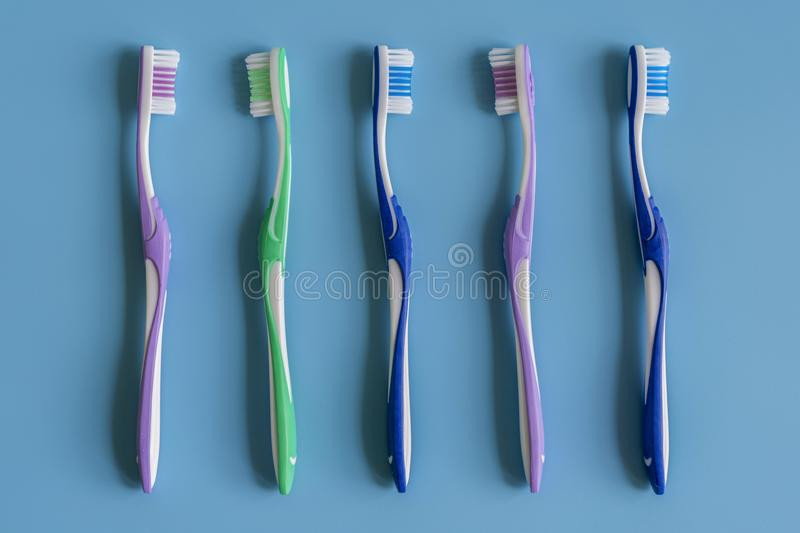 Toothbrushes on blue background. Flat lay composition with manual toothbrushes on color background, close up.  stock photos