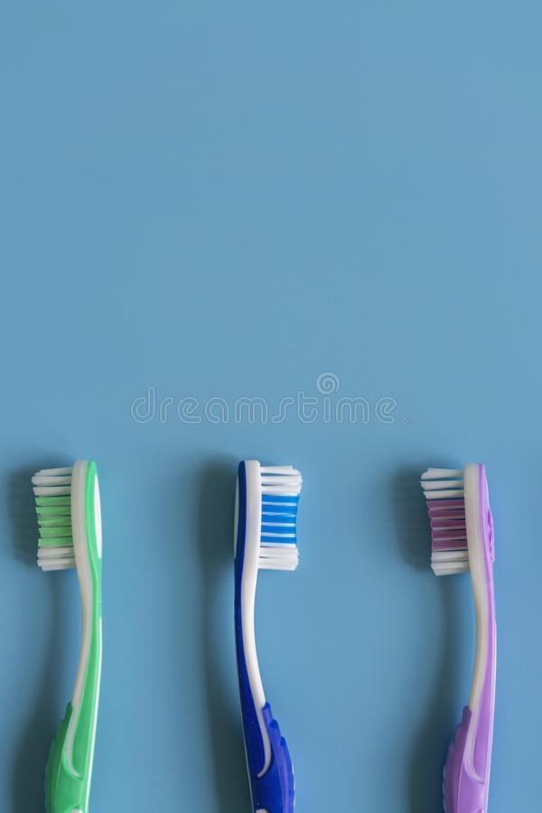 Toothbrushes on blue background. Flat lay composition with manual toothbrushes on color background, close up. vertical photo.  stock photos