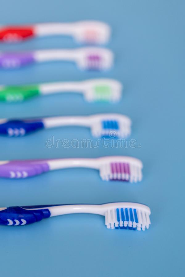 Toothbrushes on blue background. Flat lay composition with manual toothbrushes. Multi-colored toothbrushes on a blue background. Close up. vertical photo stock photos