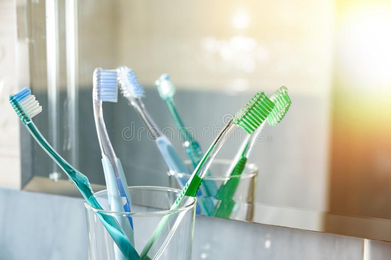 Toothbrushes in a glass vase in bathroom reflected in mirror. Toothbrushes in a glass vase in a blue bathroom in front of a mirror. Horizontal composition. Front stock image