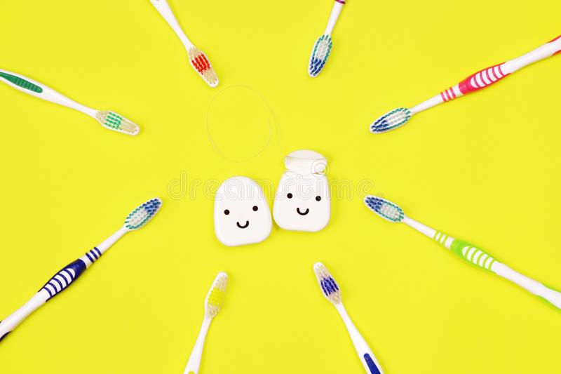 Toothbrushes i stomatologiczny floss na żółtym tle obraz royalty free