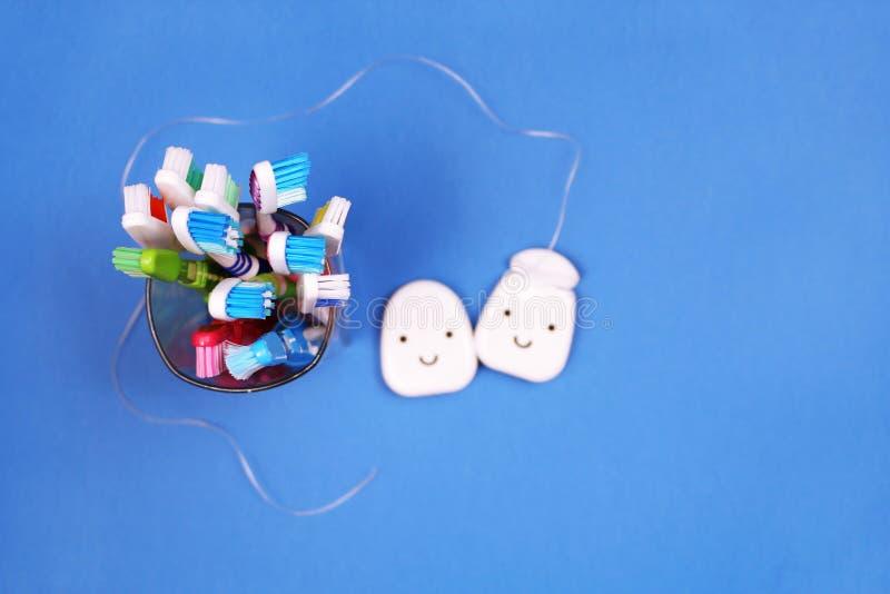 Toothbrushes i stomatologiczny floss na błękitnym tle obraz stock