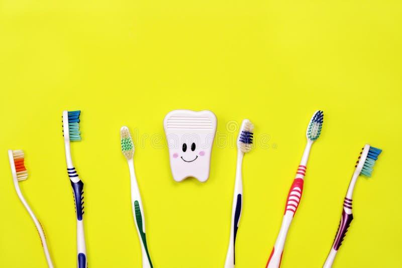 Toothbrushes i zabawkarski ząb na żółtym tle zdjęcie royalty free
