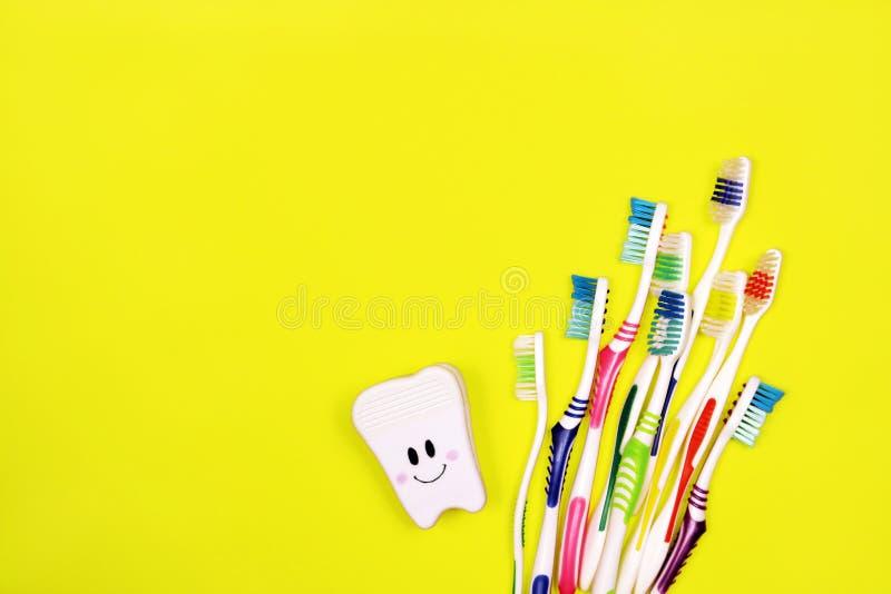 Toothbrushes i zabawkarski ząb na żółtym tle fotografia stock
