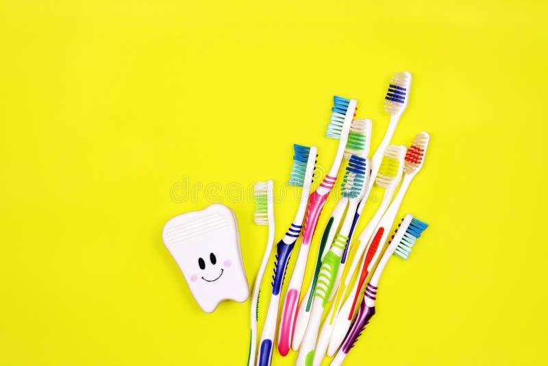 Toothbrushes i zabawkarski ząb na żółtym tle obrazy stock