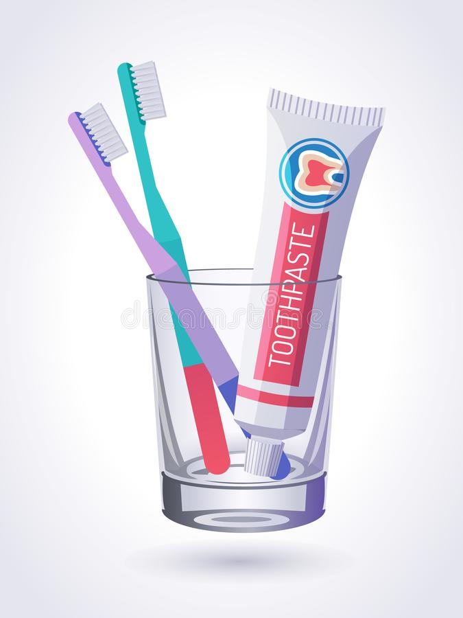 Toothbrushes and Toothpaste in transparent glass isolated on white background royalty free stock image
