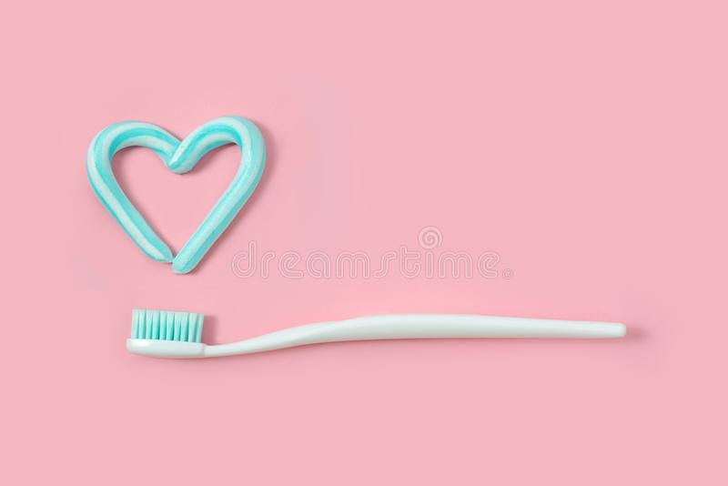 Toothbrushes and turquoise color toothpaste in shape of heart on pink background. Dental and healthcare concept. stock photos