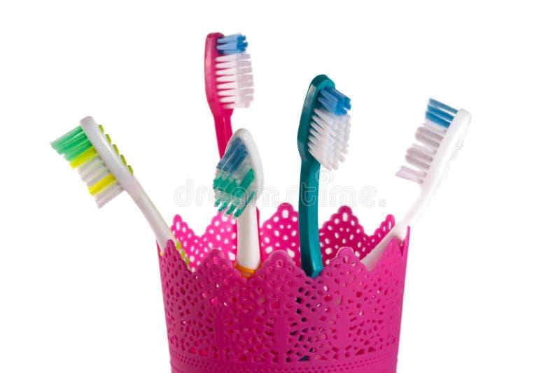 Toothbrushes w różowym szkle odizolowywającym na białym tle zdjęcie stock