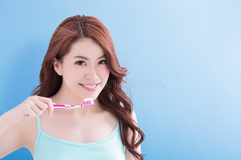 Toothbrushs de la toma de la mujer de la belleza foto de archivo