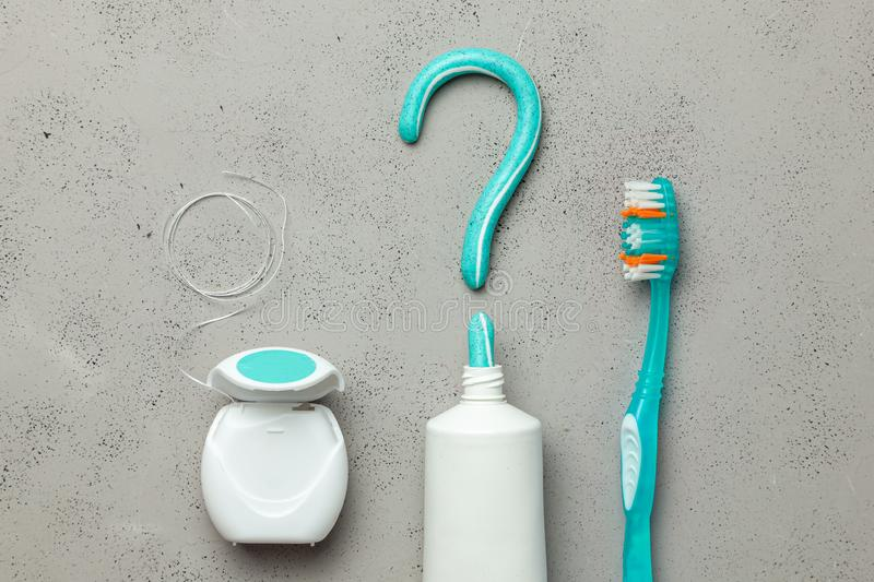 Toothpaste in the form of a question mark and toothbrushes and dental floss. Concept of how to choose the right toothbrush or how royalty free stock images