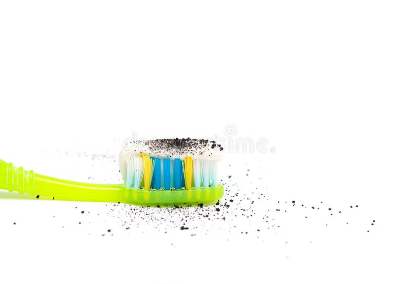 Toothpaste on a toothbrush with the addition of activated charcoal to better clean the teeth, close-up, white background, isolate. Copy space, absorbent carbon stock photo