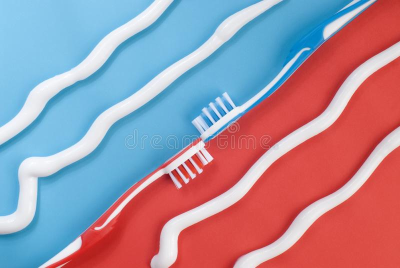 Toothpaste and toothbrushes on red and blue. Background. Tooth cleaning concept royalty free stock photography