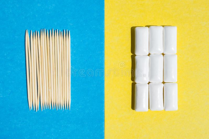 Toothpicks on blue background and group chewing gums in white container on yellow backdrop, top view stock photography