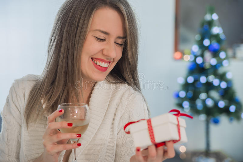 Toothy glimlachende vrouw die met rode lippen giftdoos en wijnstokglas houden stock foto's