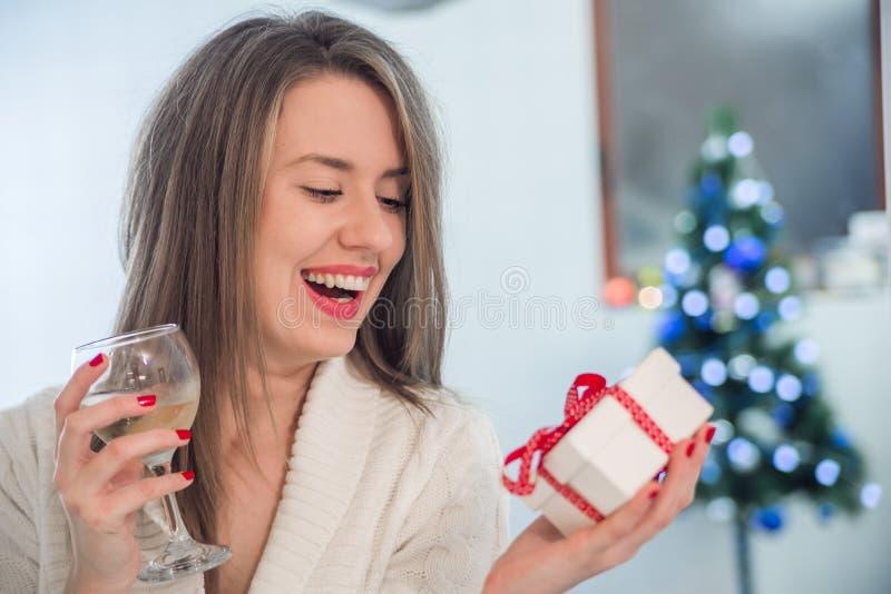 Toothy glimlachende vrouw die met rode lippen giftdoos en wijnstokglas houden stock afbeeldingen