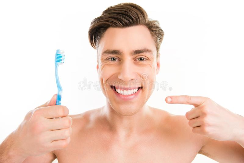 Toothy happy young man pointing on blue toothbrush royalty free stock photography