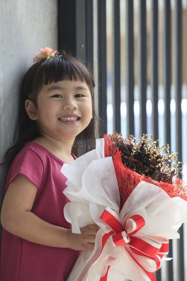 Toothy het glimlachen gezicht van de Aziatische emotie van het jong geitjegeluk en droge flowe royalty-vrije stock foto