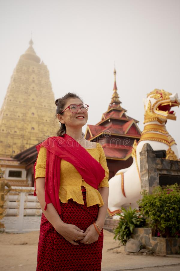 Toothy lächelnde Gesichtsstellung der Asiatin vor Buddhismuspagode in kanchanaburi eins des meisten populären reisenden Bestimmun stockfotos