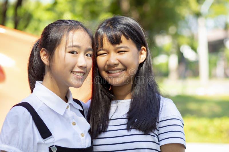 Toothy lächelndes Gesicht der asiatischen Stellung des Jugendlichen zwei im Freien stockbilder