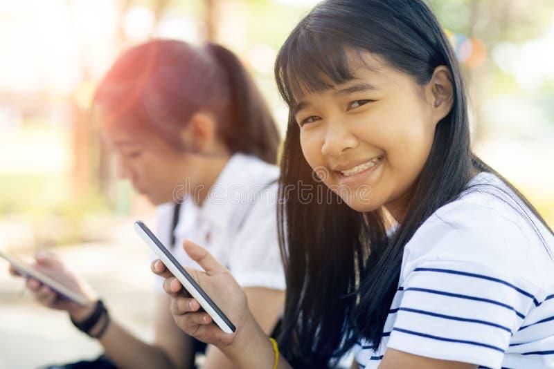 Toothy lächelndes Gesicht des netten asiatischen Jugendlichen, der in der Hand intelligentes Telefon hält stockfotografie