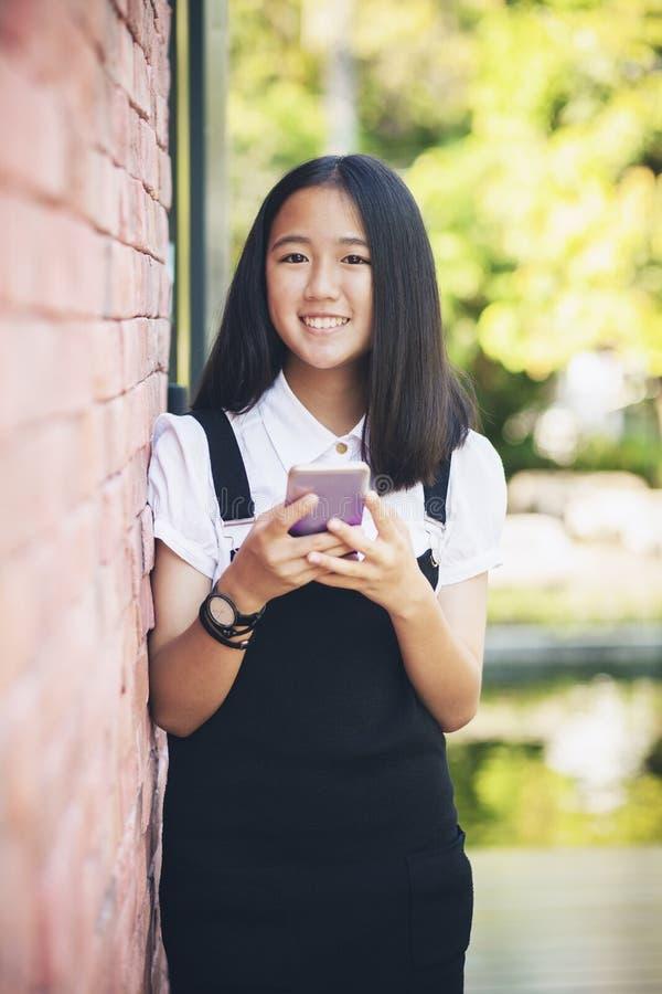 Toothy lächelndes Gesicht des schönen asiatischen Jugendlichen unter Verwendung des smarphone herein lizenzfreie stockfotos