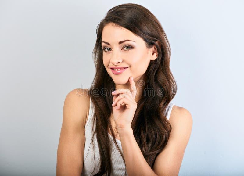 Toothy le kvinna f?r h?rlig naturlig makeup med l?ng h?rstil Skincare begrepp Closeupst?ende p? bl? bakgrund arkivfoton