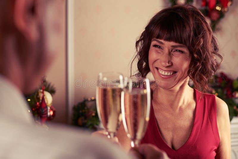 Toothy skratta för champagneflöjter för hög kvinna hållande selebratin arkivbilder