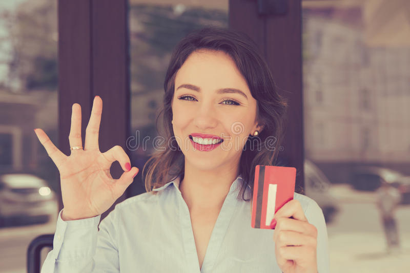 Toothy smile woman holding showing credit card near office store shopping mall outdoors. royalty free stock image