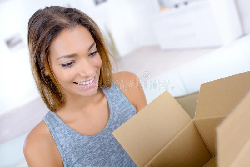 Toothy smile woman opening parcel at home stock images