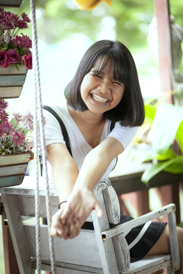 Toothy smiling face of asian teenager sitting on wood desk stock photos