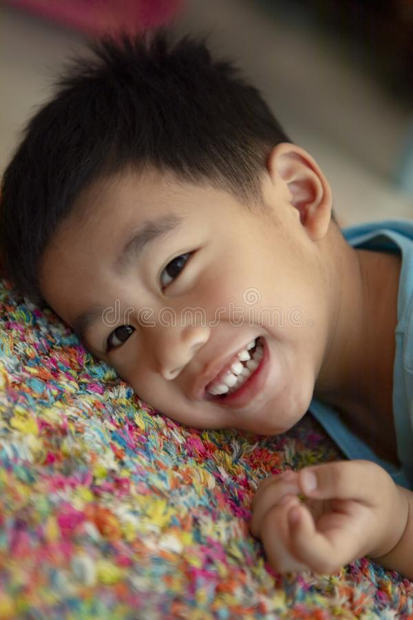 Toothy smiling face of asian toddler lying on floor. Toothy smiling face of asian  toddler lying on floor stock photos