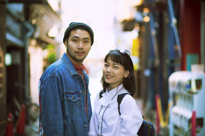 Toothy smiling face of asian younger man and woman in city life location stock images
