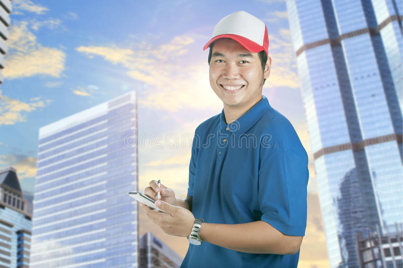 Toothy smiling face of delivery man and smart computer in hand p royalty free stock image