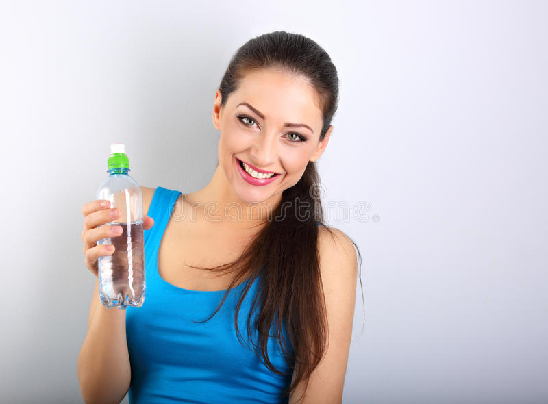 Toothy smiling happy beautiful woman holding the bottle of pure stock images