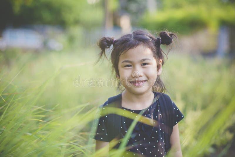 Toothy uśmiechnięta twarz azjatykci dzieci stoi w zieleni opuszcza f obraz royalty free