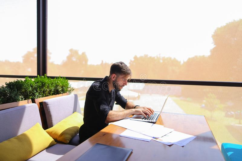 Topógrafo de cantidad que trabaja en la tabla del café con los papeles y el ordenador portátil fotografía de archivo libre de regalías