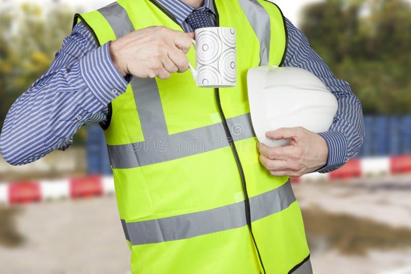 Topógrafo del edificio en hola fuerza con el casco que tiene un descanso para tomar café foto de archivo