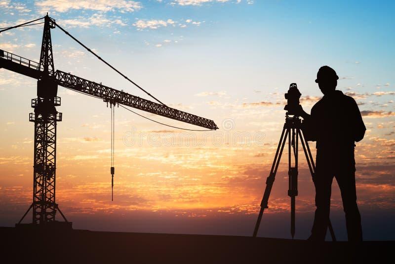 Topógrafo Standing With Equipment en el emplazamiento de la obra foto de archivo