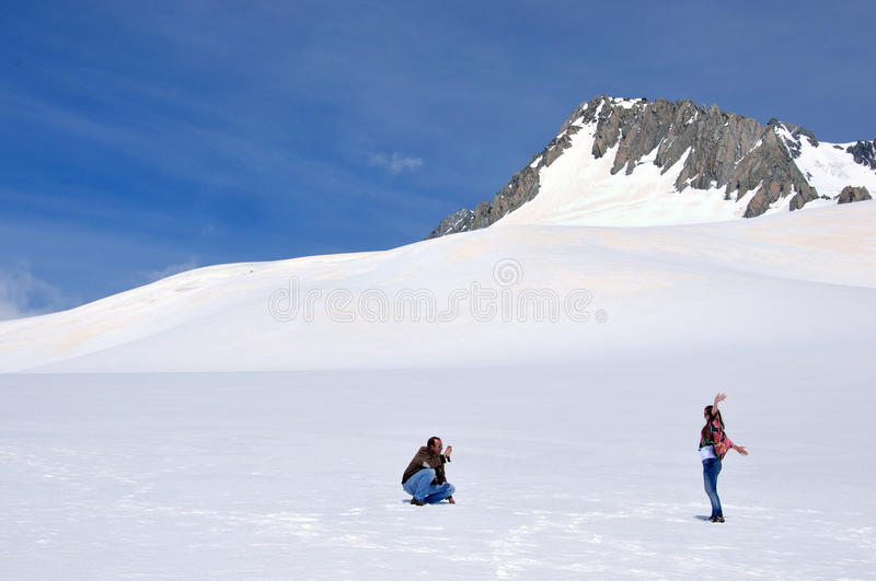 On the top. FRANZ JOSEF GLACIER, NEW ZEALAND: DECEMBER 24, 2009: Unidentified couple taking photos on the snow above Franz Josef Glacier, Westland, New Zealand royalty free stock photo