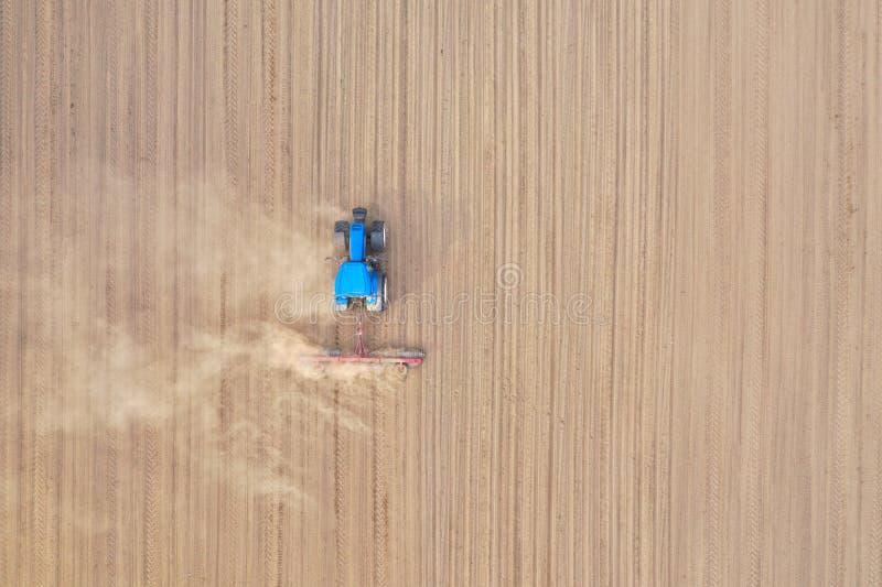 Top aéreo abajo de la opinión sobre el tractor azul que tira de una paleta, preparando un suelo para la siembra de la semilla, tr imagenes de archivo
